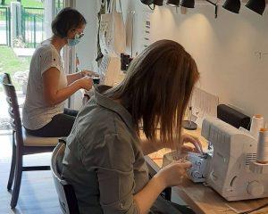 Apprendre la couture à plusieurs chez Etoffe de soi, photo souvenir de deux personnes en train de manipuler des surjeteuses